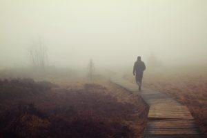man walking on hazy day