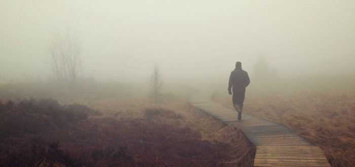 man walking on hazy day